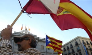 A demonstrator waves a Spanish national flag in front of a Catalonian pro-independence one in Barcelona.