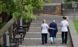 two nurses escort an elderly patient through the hospital grounds