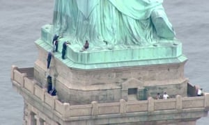 This still image taken from video courtesy of PIX11 News in New York shows police talking to a woman who has climbed to the base of the Statue of Liberty in New York