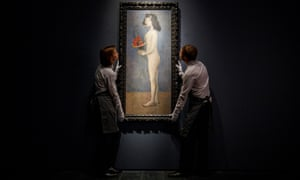 Gallery assistants with the Picasso painting Young Girl with a Flower Basket, which fetched $115m, the second-highest price at auction for the artist.