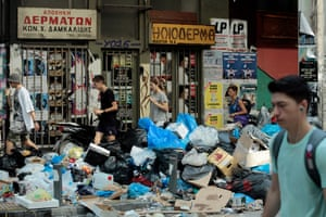 Tourists walk past rubbish festering in soaring temperatures in Athens
