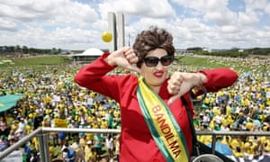 An impersonator of Dilma Rousseff gives a thumbs-down hand gesture during a protest outside the National Congress building in Brasilia.