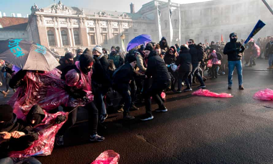 Protesters try to break through police barricades near the presidential palace in Vienna