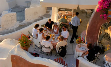 Diners in a picturesque restaurant with ocean view, in Oia.