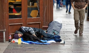 A homeless man sleeps outside a Greggs in the centre of Cardiff, UK