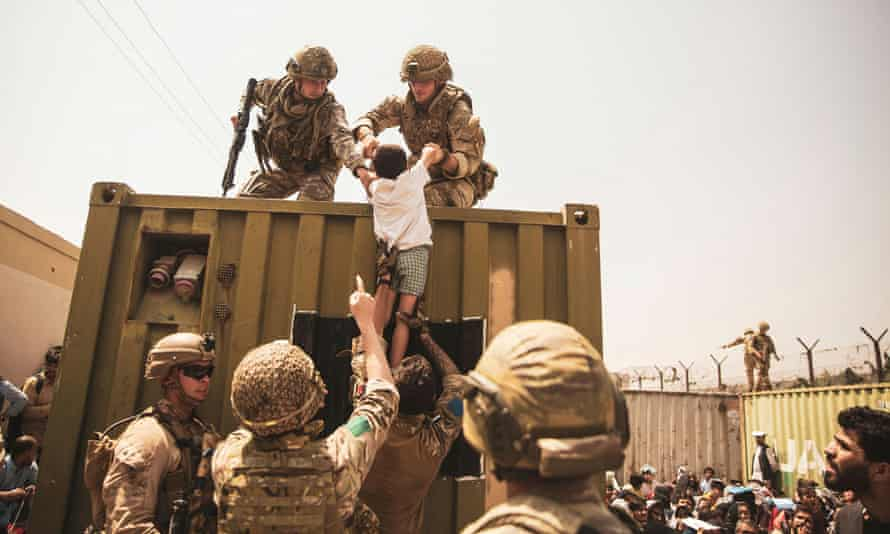 Western forces assist a child during an evacuation at Kabul airport on 20 August