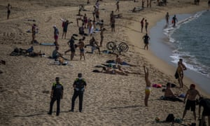 Police officers stand at the beach as they ask people to not sit, in Barcelona, Spain, 3 June. 2020. Spain's Health Ministry says it recorded no deaths from Covid-19 on Wednesday, for a second day in a row.