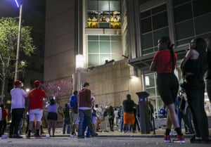 Inmates chant and throw things from broken windows at the city's prison, the Justice Center, as crowds look on