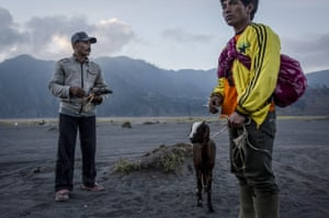Villagers carry livestock to volcano