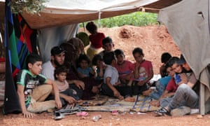 A displaced family shelters in an olive grove in the town of Atmeh, Idlib province