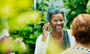 Laughing woman hanging out with friends during backyard dinner party