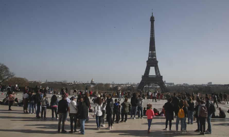 People wearing wearing face masks gather at the Trocadéro plaza near the Eiffel Tower, Paris.