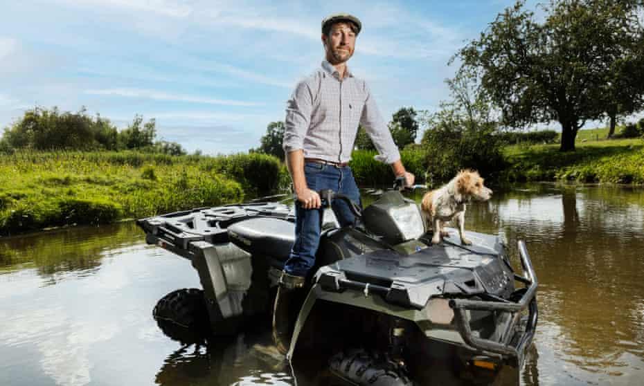 Joe Garland with his dog Pebbles on a quad bike at Mythe Farm in Warwickshire.