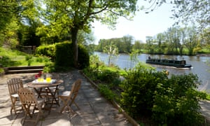 the Thames sweeps past the patio outside Ferry Cottage, Cliveden.