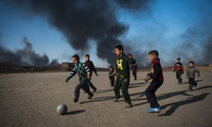Oil wells smoulder in the background as children play football in Qayyarah, south of Mosul