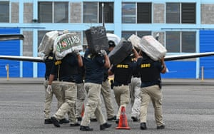Tegucigalpa, Honduras: Criminal investigation agents carry packages seized from the mayor of the island of Roatan, Jerry Hynds, after his arrest on drug smuggling charges
