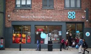 People walk past a Co-op supermarket in London.