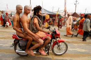Juna Akhara sect members catch a ride with their tutor at the Maha Kumbh festival. They were to attend rituals to become Naga, naked holy men with no worldly ties.
