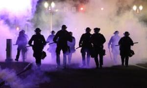 Policemen walk enveloped by teargas in Portland, Oregon.