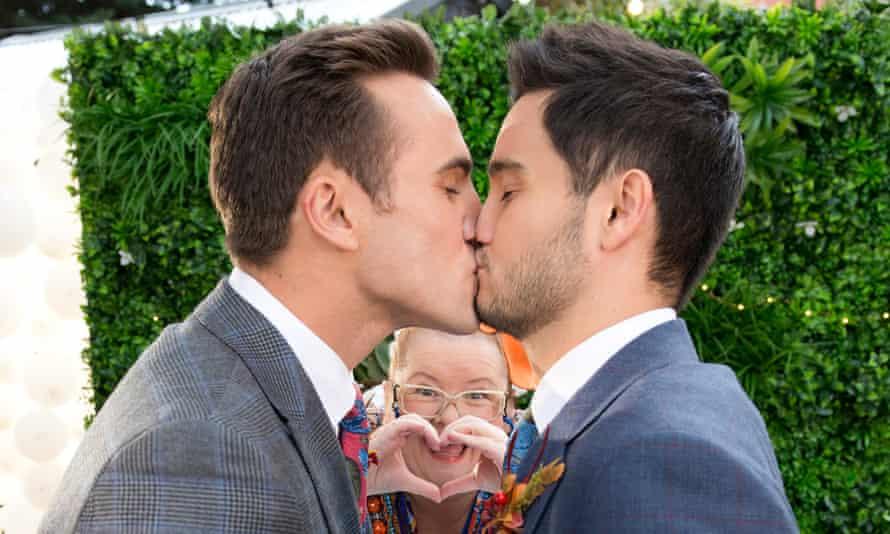 David (Takaya Honda) and Aaron (Matt Wilson) kiss after their nuptials.