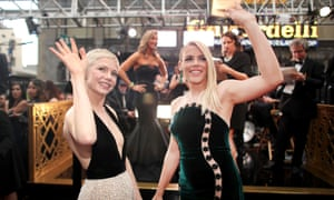 Busy Philipps and Michelle Williams turning towards the camera and waving