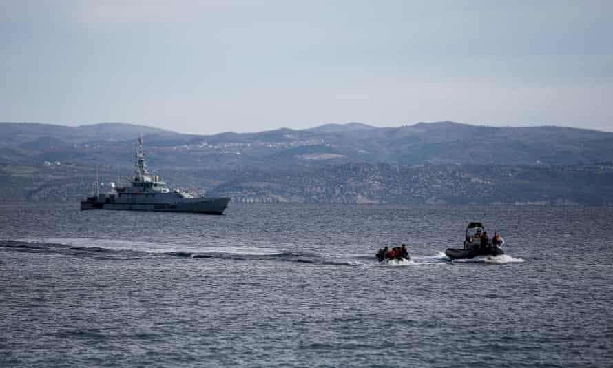 A rescue boat escorts a dinghy with migrants from Afghanistan as a Frontex ship patrols off Lesbos in Greece.