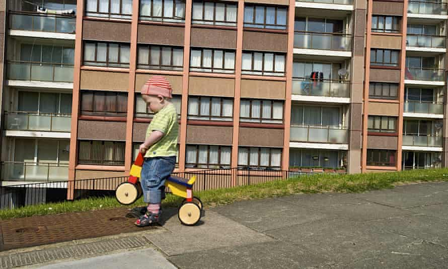 Small boy playing in front of Whitehawk housing estate