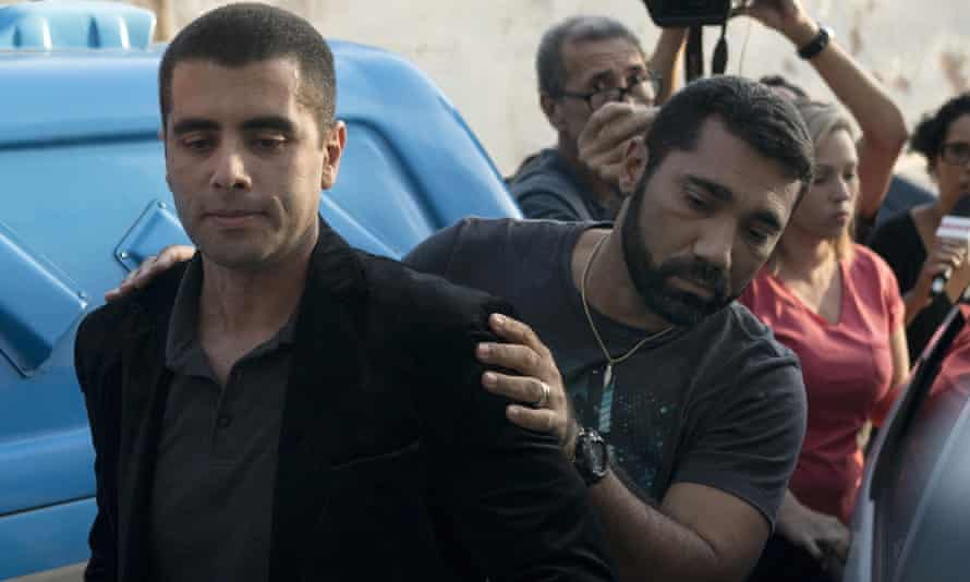 Denis Furtado is escorted by police after his arrest in Rio de Janeiro in July
