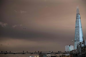 Pedestrians cross the Millennium Footbridge with the sky darkened over London caused by warm air and dust swept up by storm Ophelia.