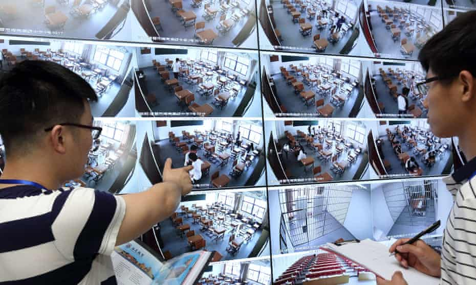 Invigilators use CCTV to inspect a classroom before the start of an exam at a school in Zhuji city, east China's Zhejiang province.