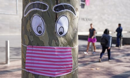 People walk past a tree with a face mask and eyes stapled to it in Melbourne.