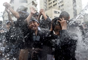 Participants are splashed with water to purify them at Fukagawa Hachimangu Festival