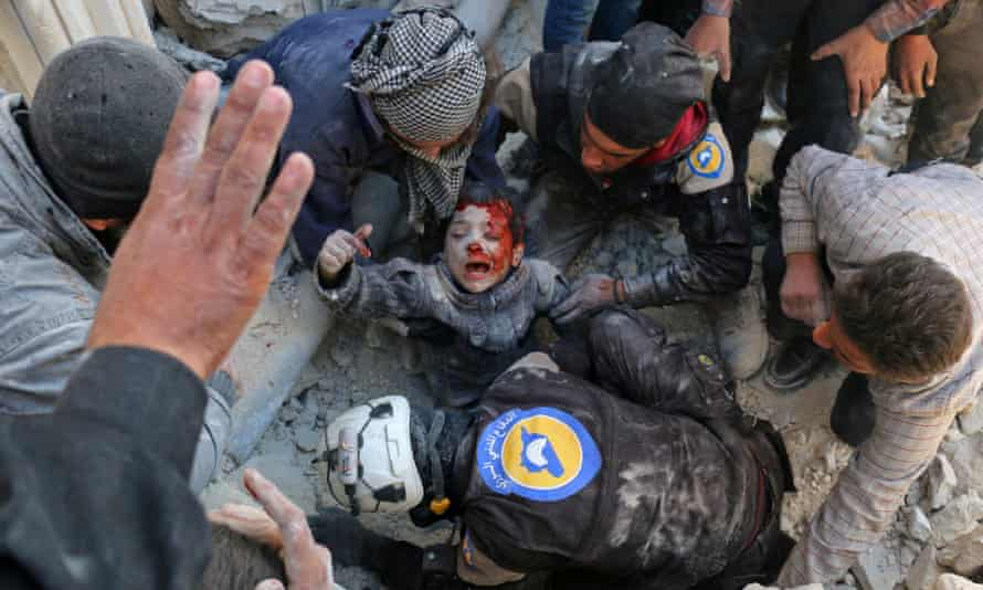 A boy is rescued from rubble following a bomb attack in Aleppo.