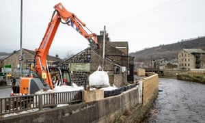 Workers construct flood defences in Mytholmroyd, West Yorkshire