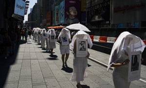 Protesters against gun violence dressed in white march in Times Square in response to recent mass shootings in El Paso, Texas and Dayton, Ohio, on Sunday in New York City.