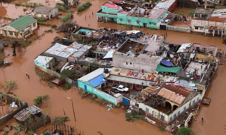 Residents stand on rooftops in a flooded area of Buzi, central Mozambique