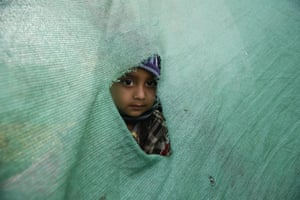 A child peeks out of a hole in a temporary tent in Kathmandu after the powerful earthquake.