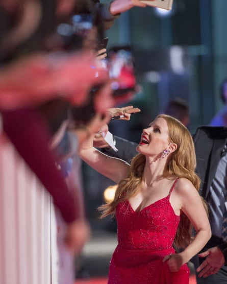 Jessica Chastain signs autographs on the red carpet.