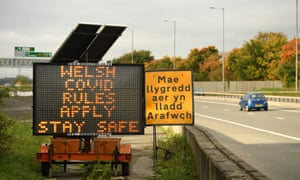 Traffic passes a 'local Covid-19 rules apply' sign displayed along the A494 near Queensferry in Flintshire.