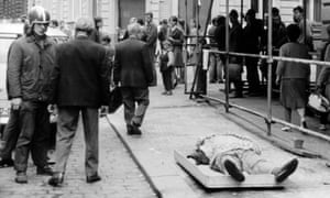 Citizens pass a body in the street.