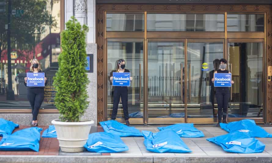 """Activists hold signs saying """"Disinformation kills"""" as they stand in front of blue body bags placed on the sidewalk in front of Facebook's office in Washington."""