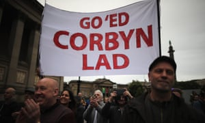 People cheer and hold placards as Labour leader Jeremy Corbyn addresses thousands of supporters in Liverpool, in August.