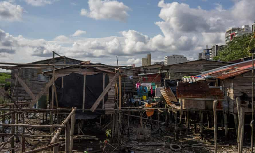 Stilt houses, known as palafitos, with modern buildings in downtown Buenaventura in the distance