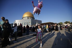 A girl walks with a balloon near the Al-Aqsa mosque compound, Islam's third most holy site