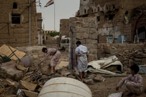 Traders search through the rubble of their shops after the market outside Imam-Hadi central mosque was destroyed by airstrikes.