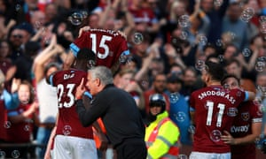 West Ham United's Marko Arnautovic celebrates scoring his side's third goal of the game by holding up a shirt with the name of Carlos Sanchez on it as Manchester United manager Jose Mourinho gestures towards the crowd.