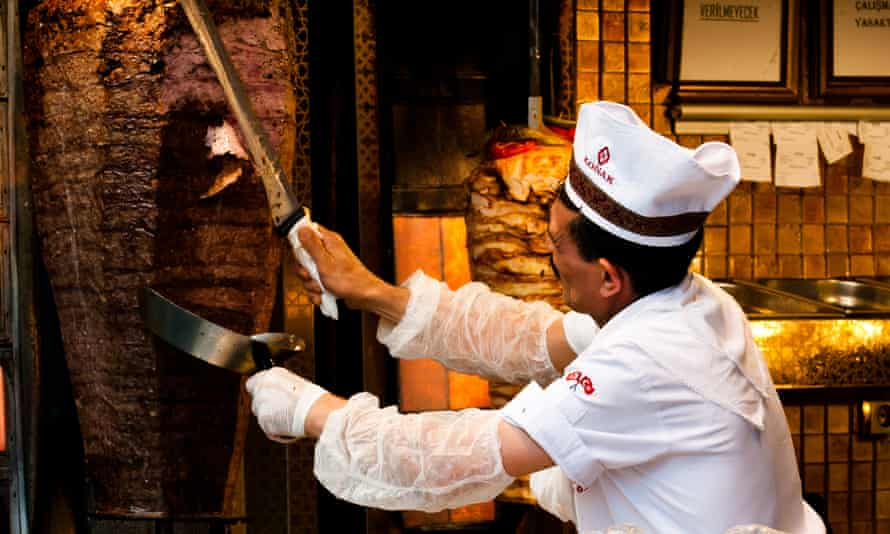 A man in white hat and overalls carving kebab in a kebab shop