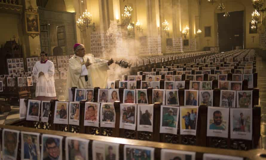 The Archbishop of Lima, Carlos Castillo, swings a censer over several of the thousands of portraits of Peru's Covid-19 victims during mass on Sunday.