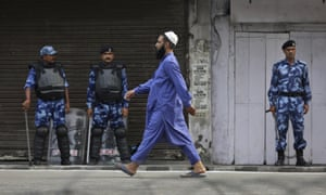 A Muslim man walks past Indian paramilitary soldiers after offering prayer during Eid al-Adha in Jammu