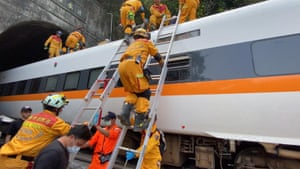 Rescuers climb on top of the train